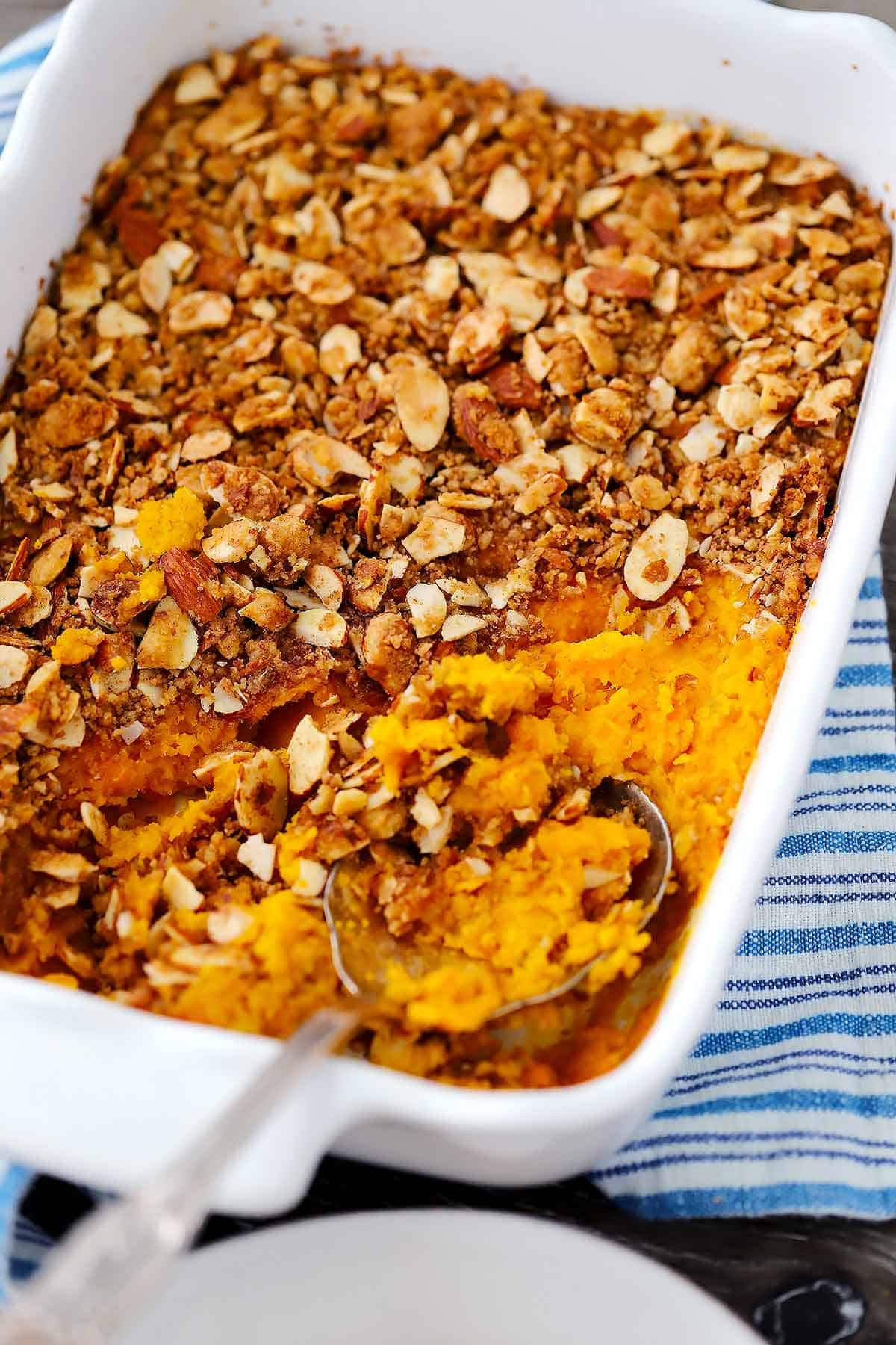 A casserole dish with sweet potato casserole and a spoon taking a scoop out.