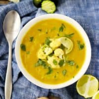 A bowl of curried cauliflower soup on a blue towel with a spoon, garnished with cauliflower florets and grated zucchini.