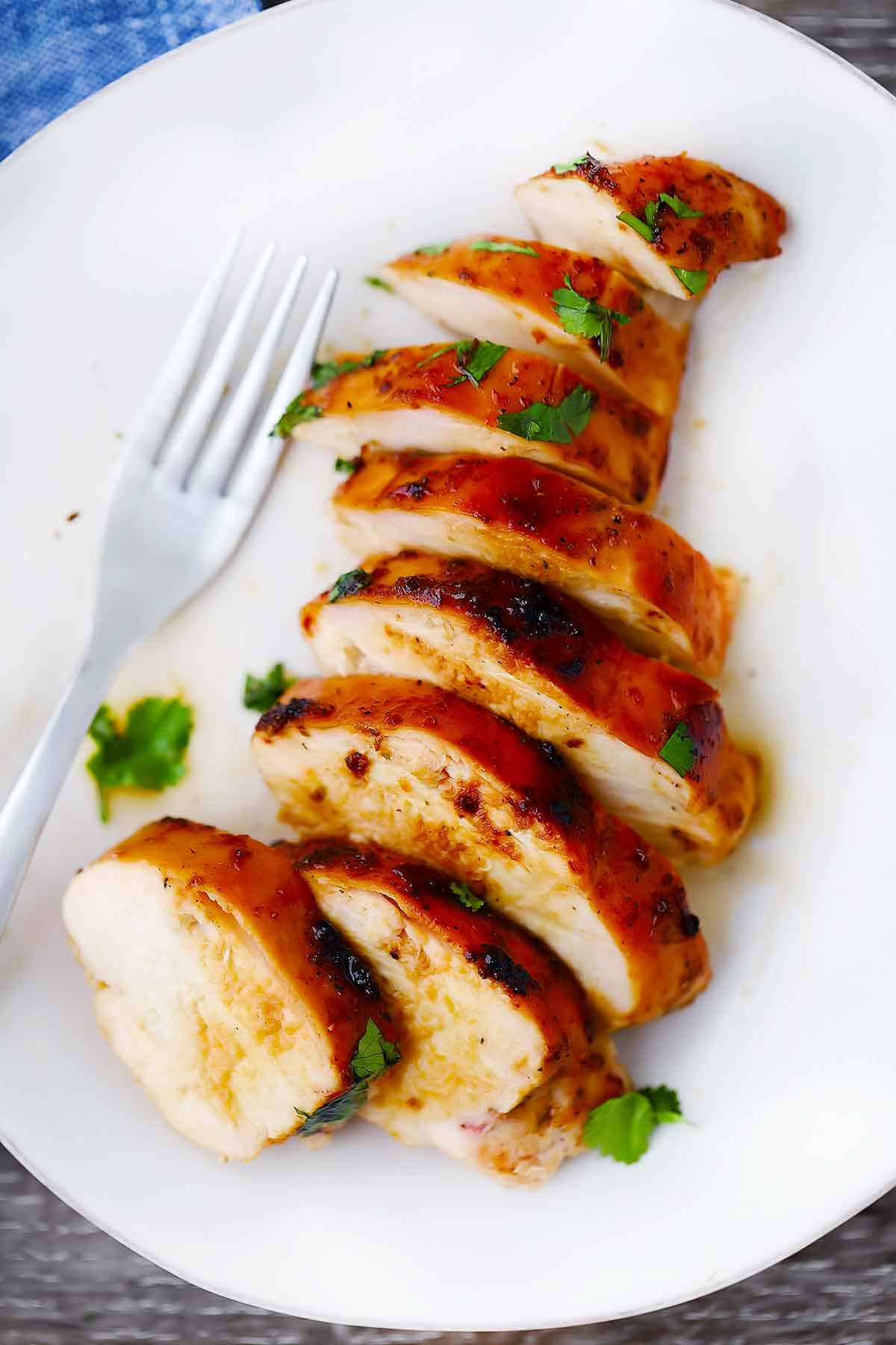 A sliced chicken breast on a white plate with a fork.