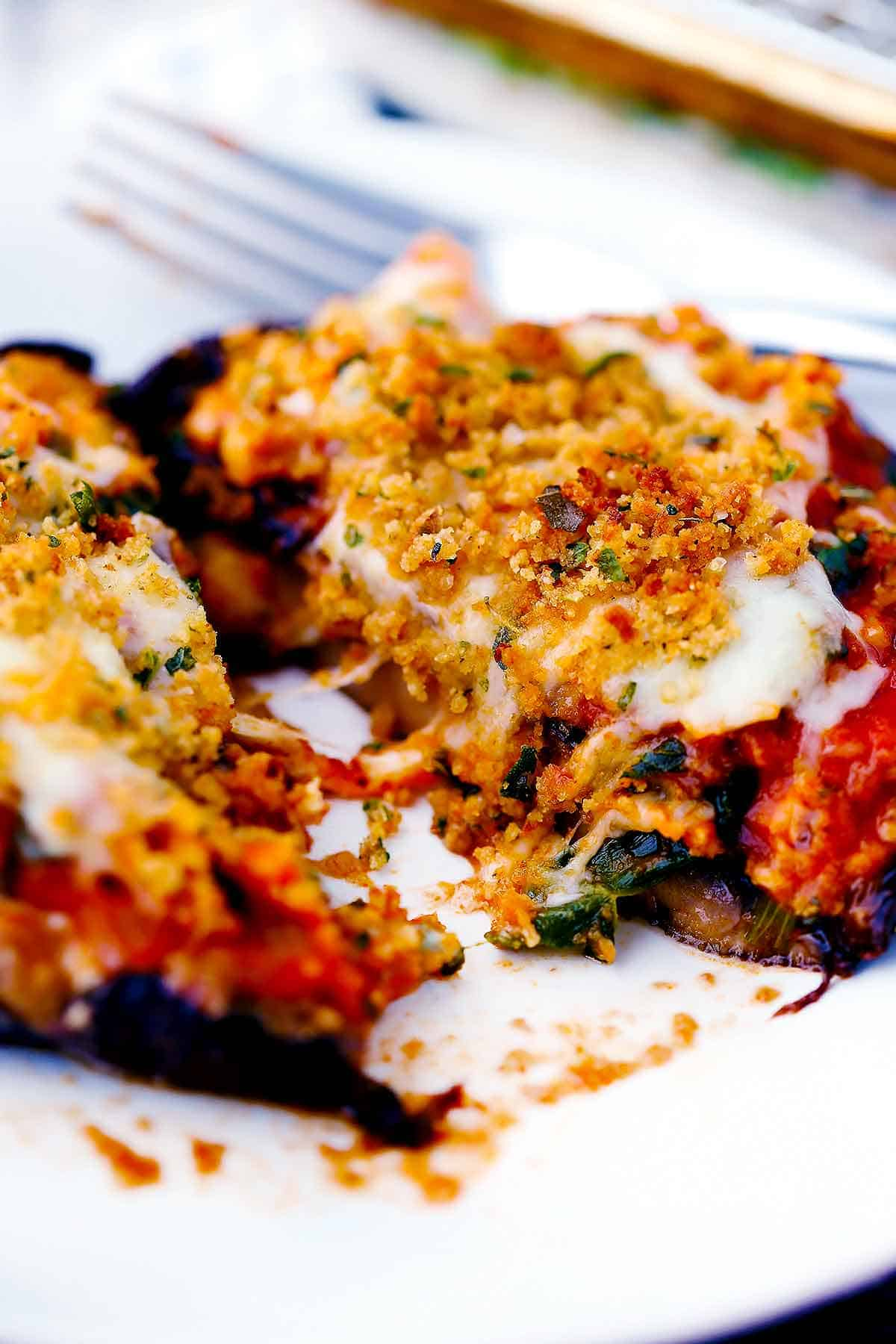 A stuffed portobello mushroom cut in half with cheese and breadcrumbs on top.