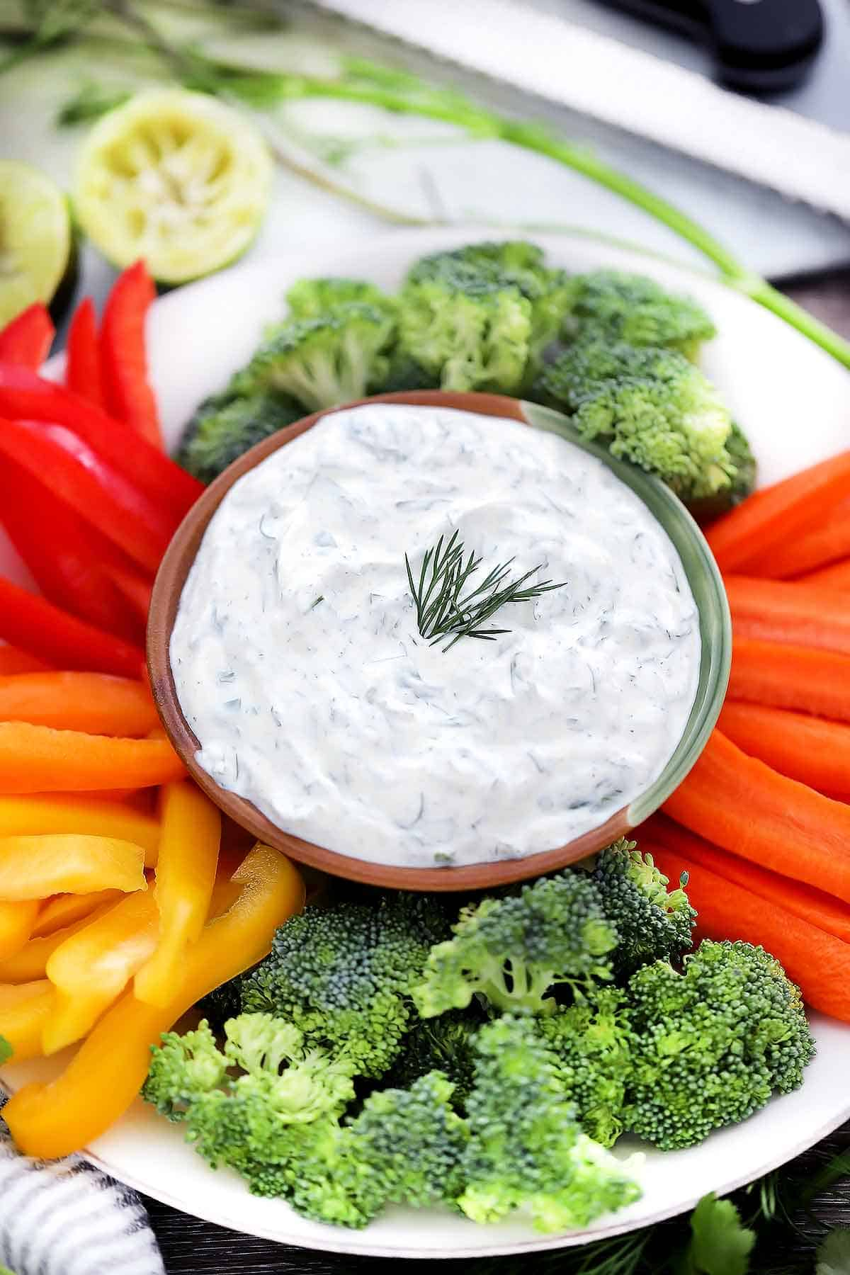 Dill dip on a plate with broccoli, peppers, and carrots.