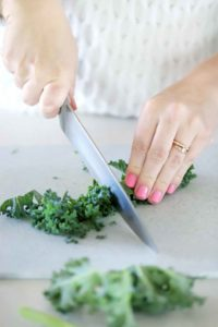 Chopping kale on a cutting board.