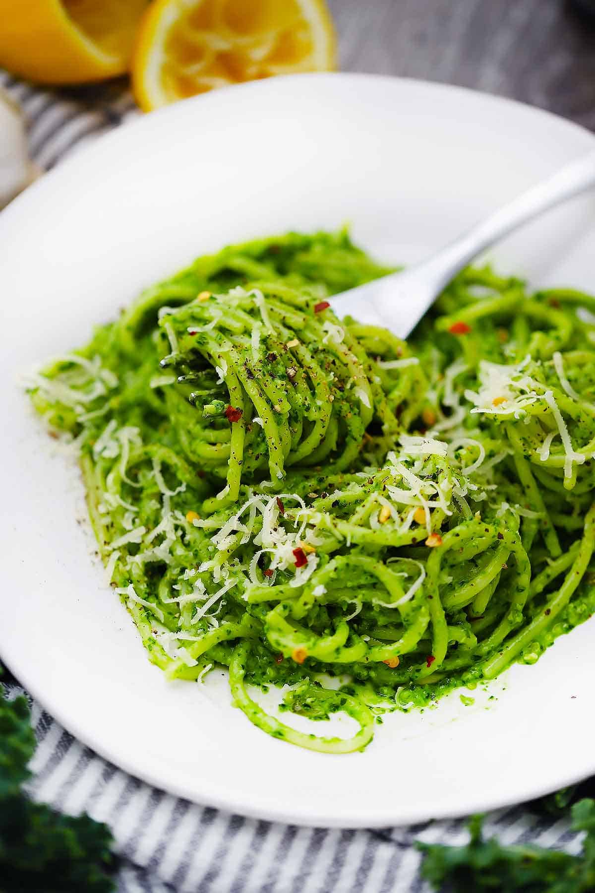 Kale pest on spaghetti on a white plate being twirled with a fork.