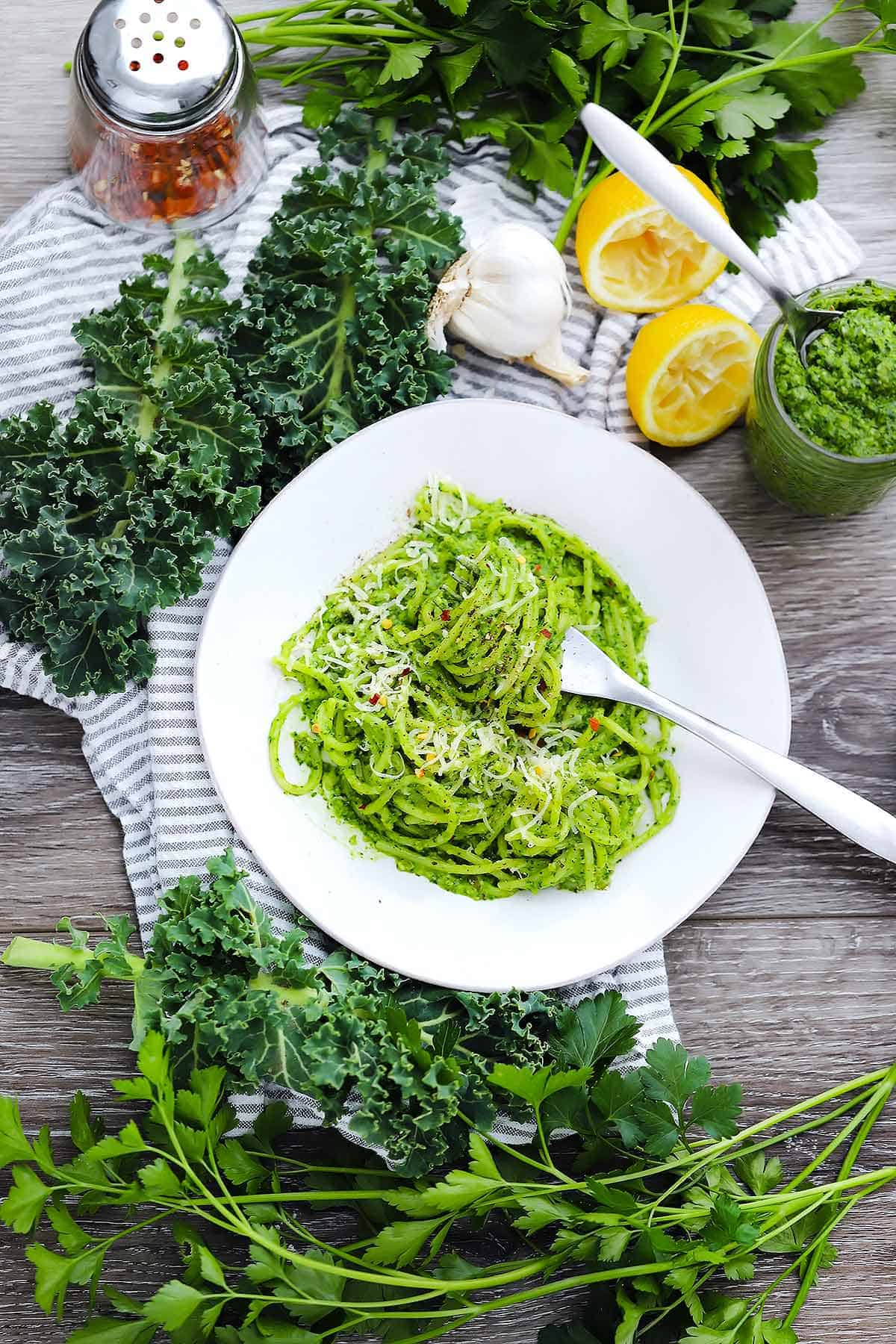 Flatlay image of spaghetti with kale pesto being twirled by a fork with kale, lemons, parsley, and red pepper in the background.