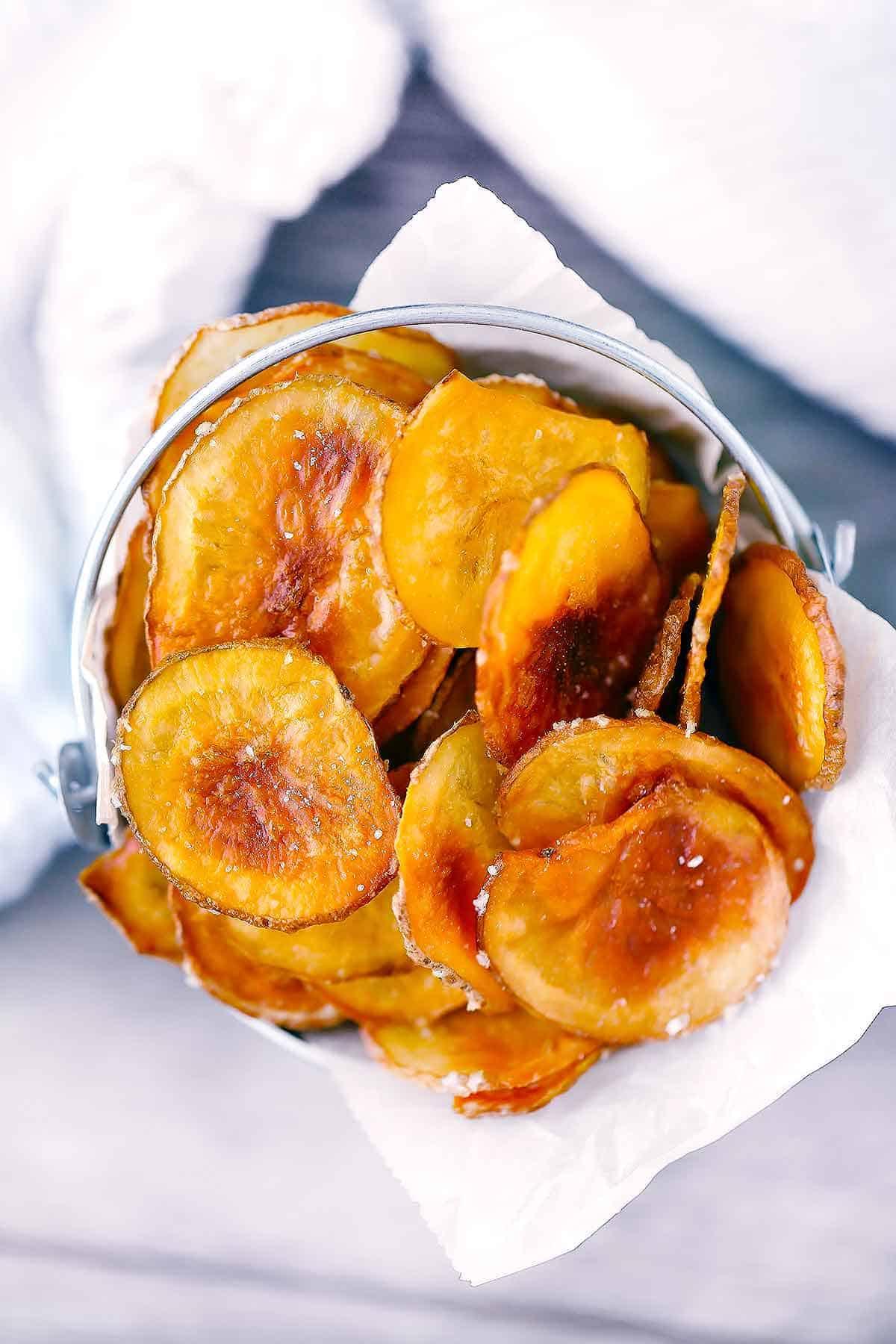 Homemade oven-baked potato chips overhead photo.
