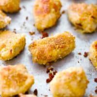 Square photo of homemade chicken nuggets on a baking sheet.