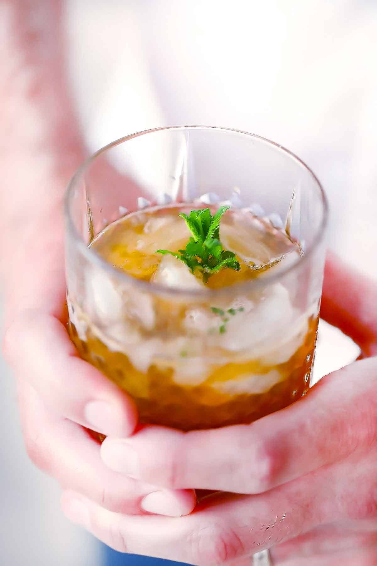 Hands holding a mint julep in an old fashioned glass.