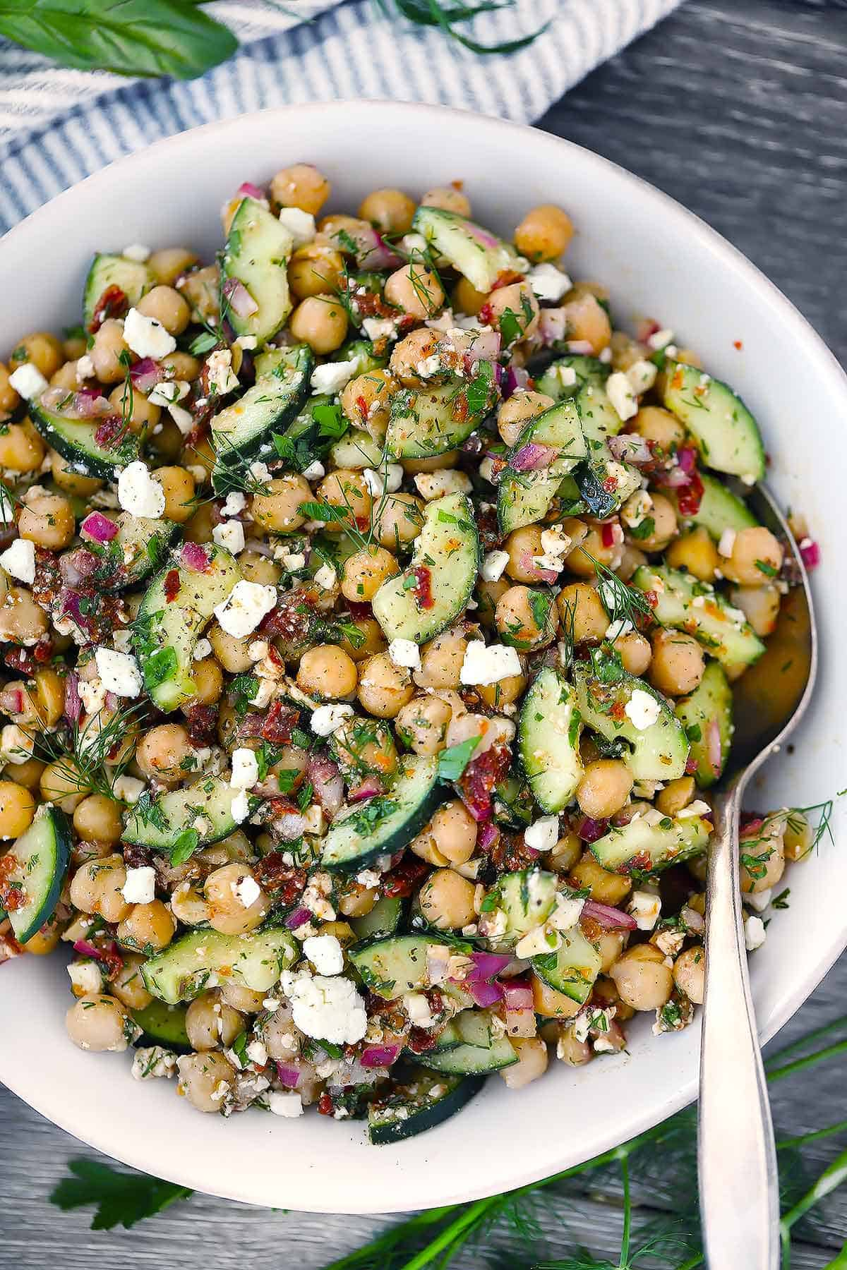 Close up photo of chickpea salad with feta cheese and cucumbers in a white bowl with a spoon.