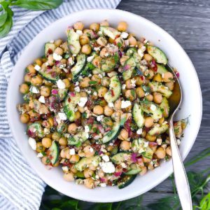 Mediterranean chickpea salad in a white bowl with a spoon in the bowl.