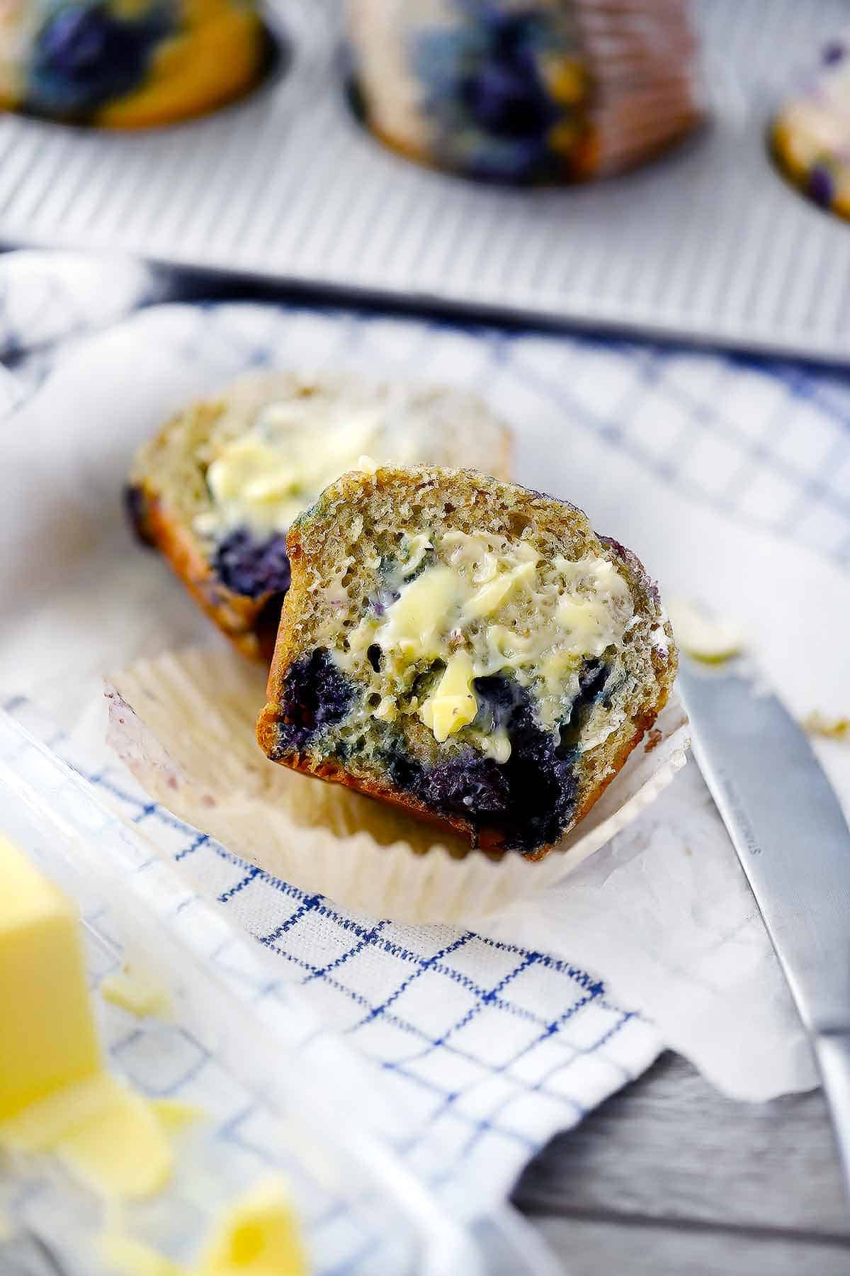 Blueberry muffin sliced in half with butter on it.