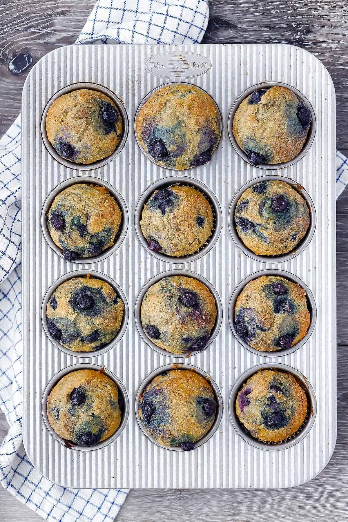 Overhead photo of a muffin pan with healthy blueberry muffins.