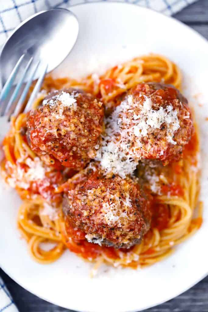 Overhead photo of spaghetti topped with three baked beef meatballs on a white plate.