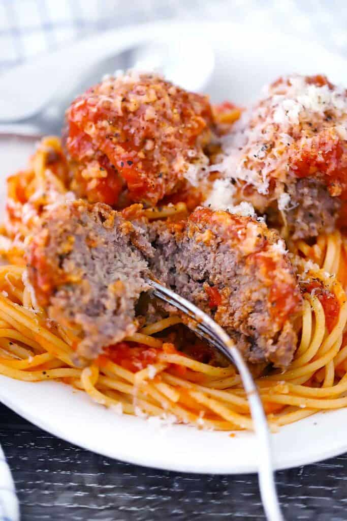 A close up photo of a meatball being cut in half with a fork on a plate of spaghetti.