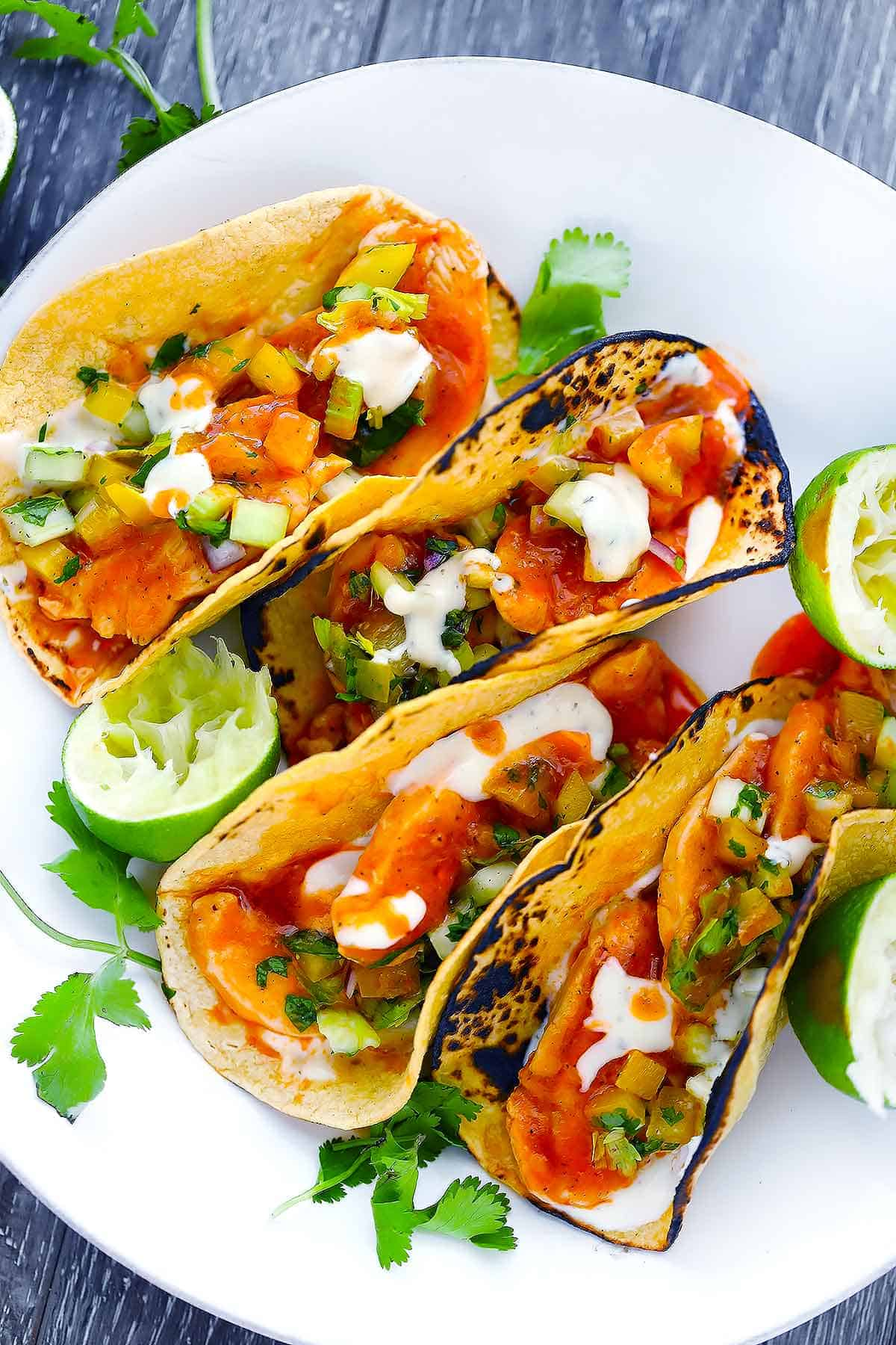 Four buffalo chicken tacos on a white plate with limes and cilantro.