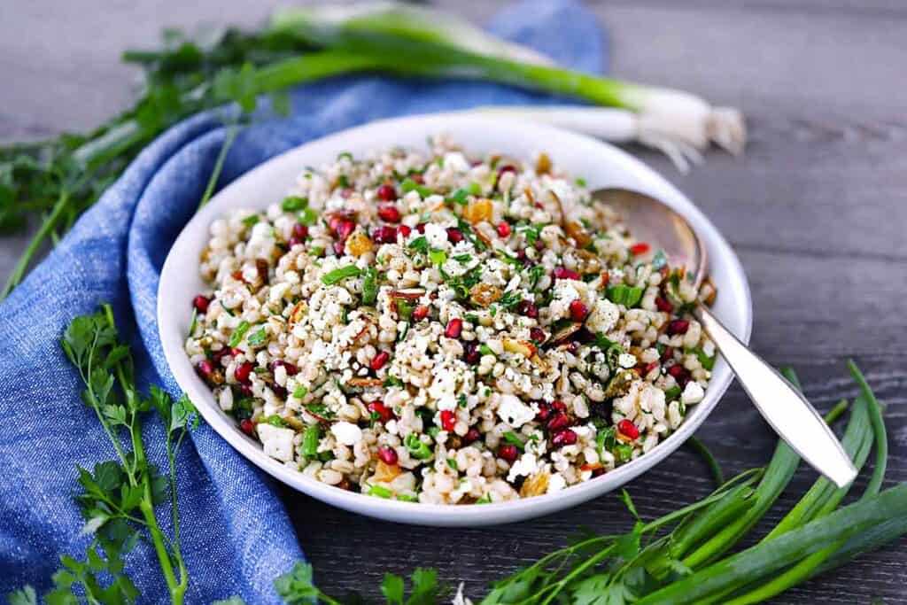 Horizontal photo of barley salad in a white bowl with green onions and a blue towel around it.