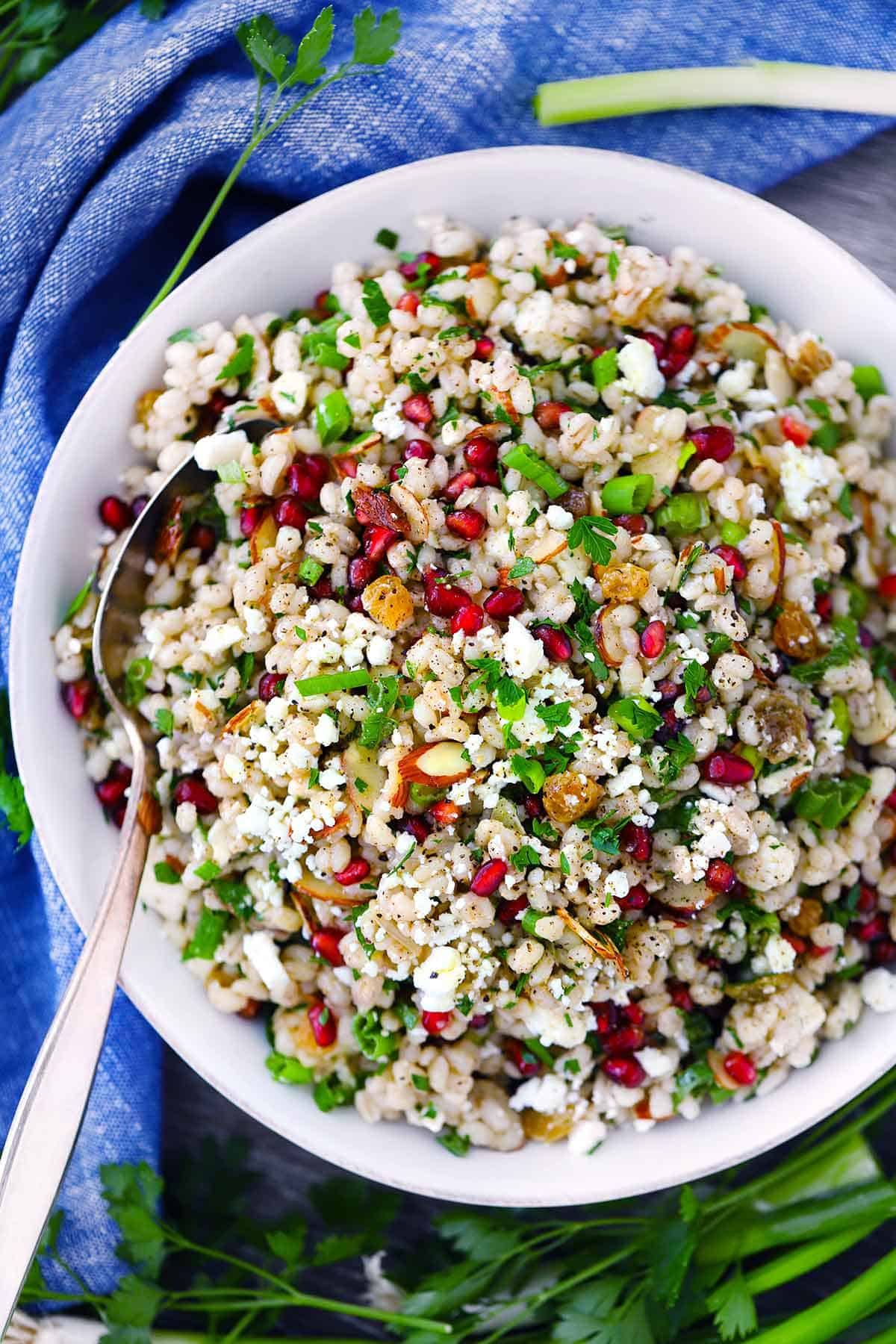 Overhead photo of barley salad with feta and pomegranate in a white bowl with a spoon on a blue towel.