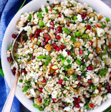 Square image of Egyptian Barley Salad in a white bowl with a spoon.
