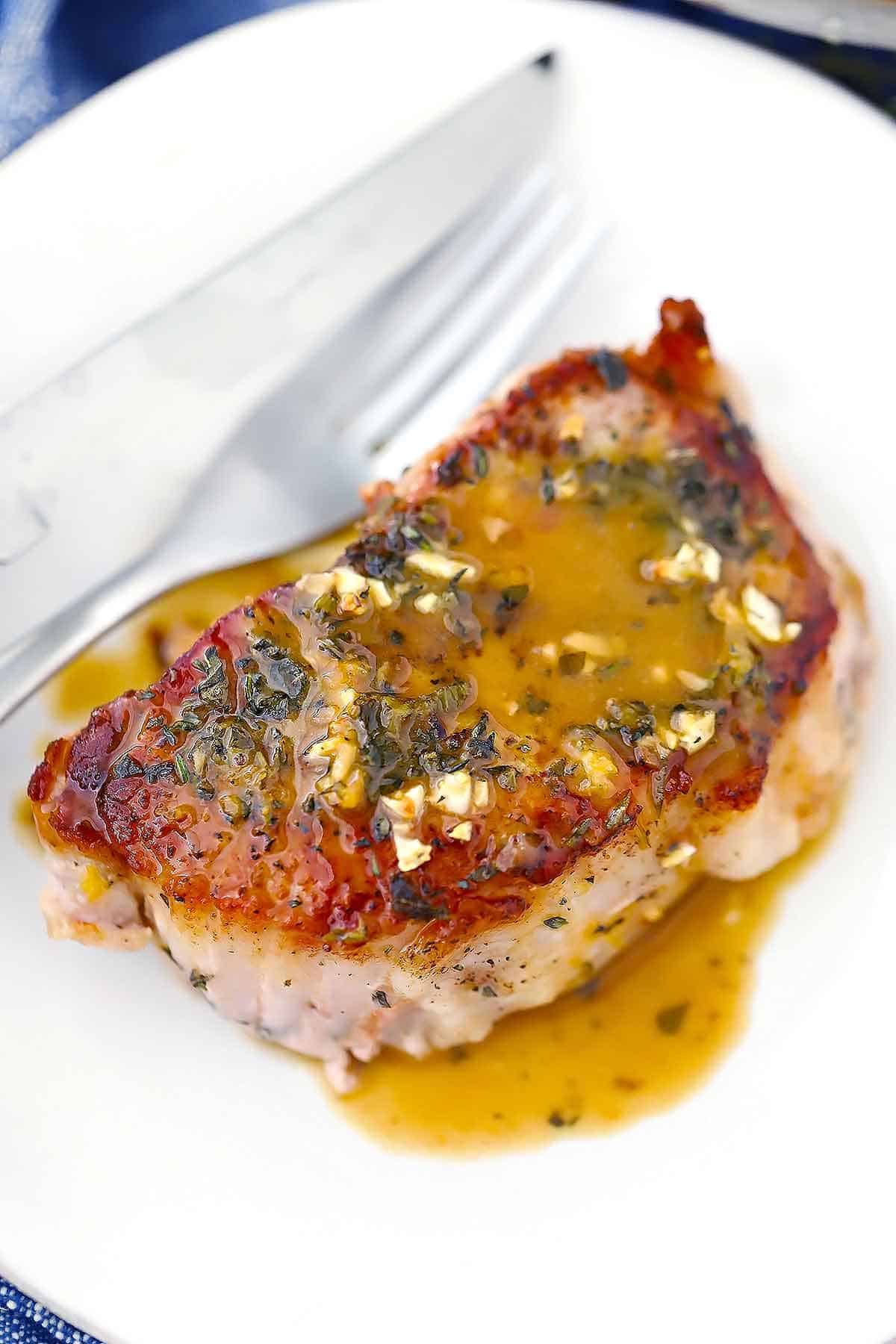 A seared oven baked pork chop on a plate with pan sauce.