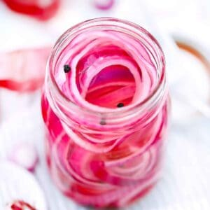 Square photo of pickled red onions in a jar.