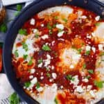 Square photo of shakshuka in a skillet.