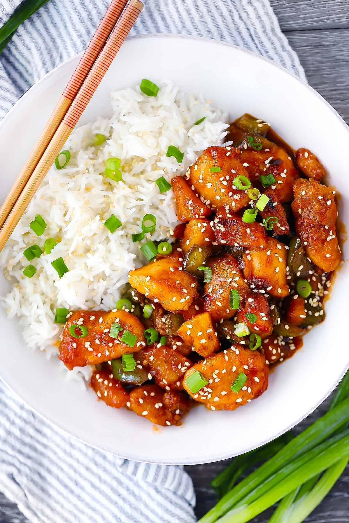 Overhead photo of a white plate with sweet and sour chicken and rice with chopsticks.
