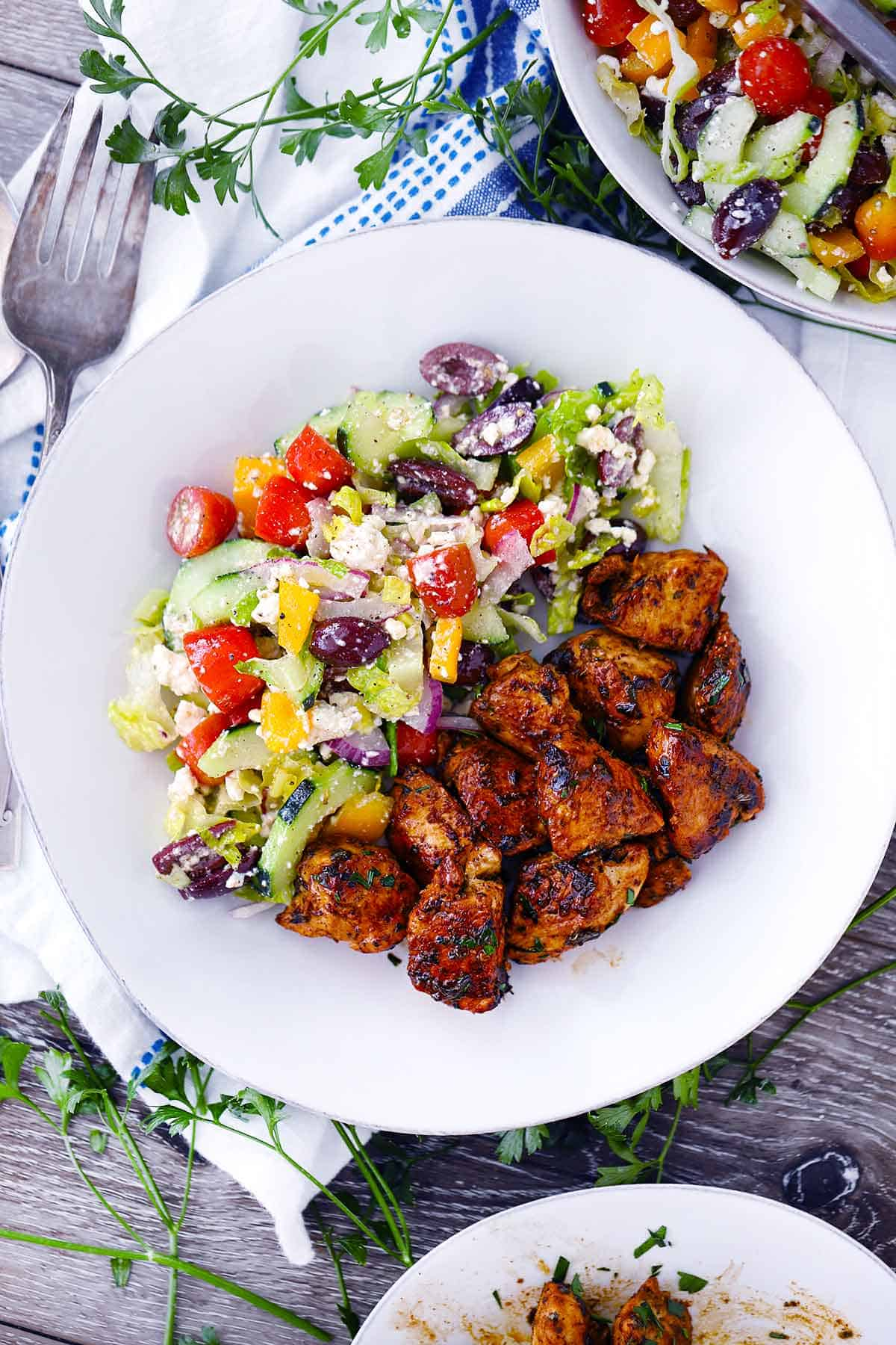An overhead photo of Greek Chicken Bites and a Greek salad on a white plate.