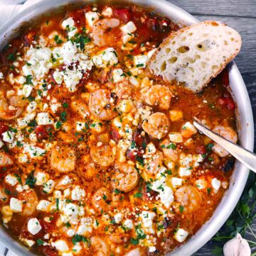 Square photo of greek shrimp with feta and tomatoes.