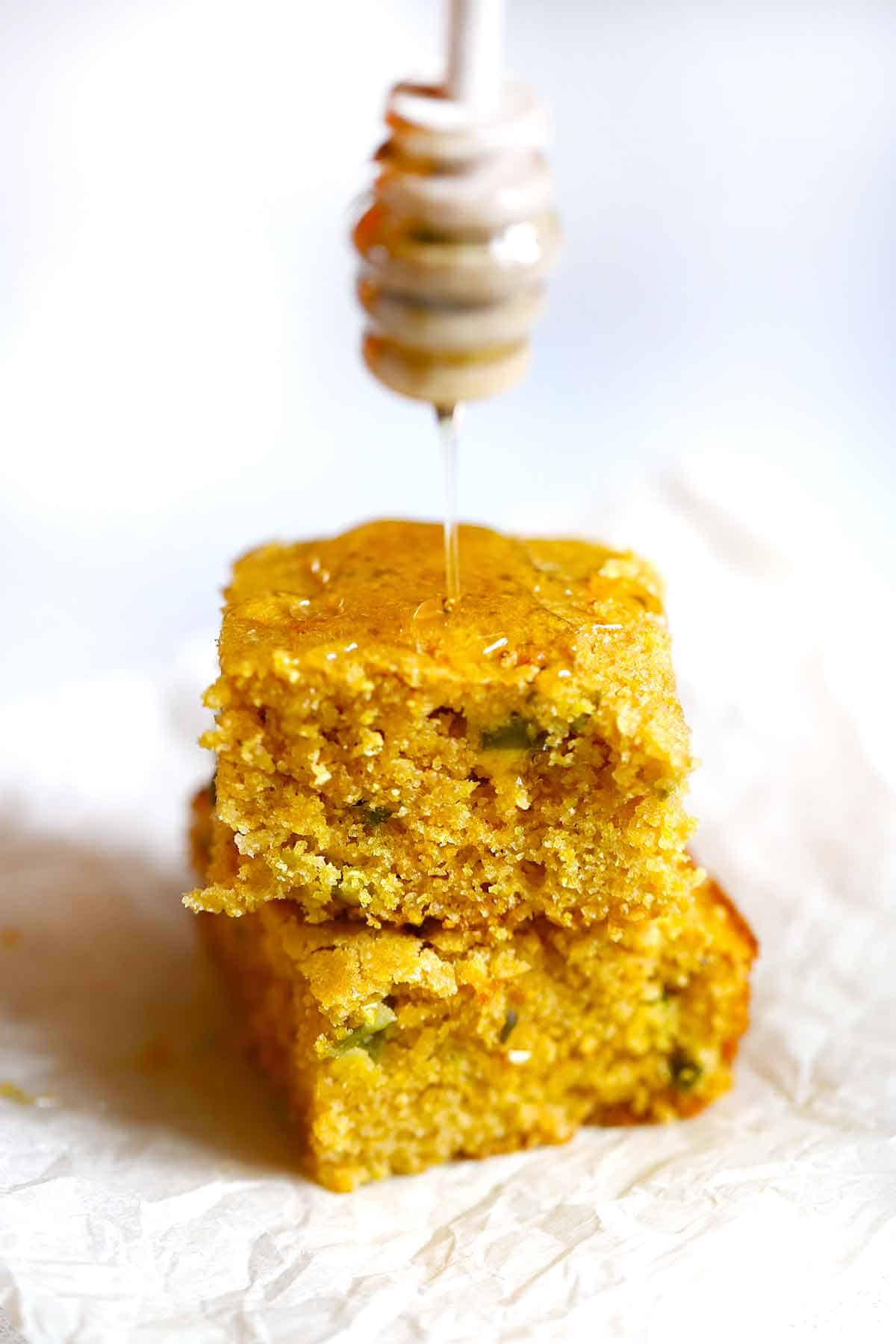 Two stacked pieces of jalapeño cornbread being drizzled with honey.