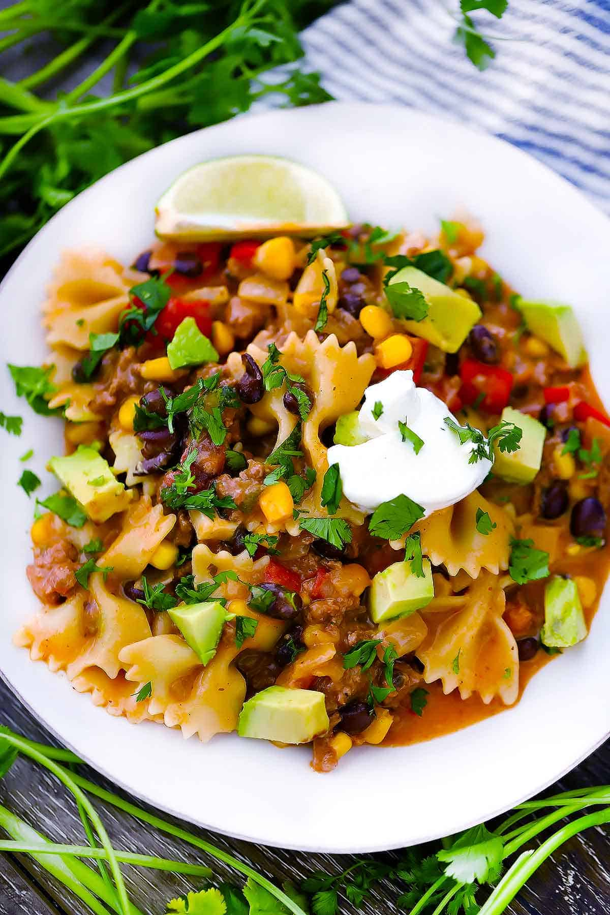 A plate of taco pasta with sour cream and avocado on top.