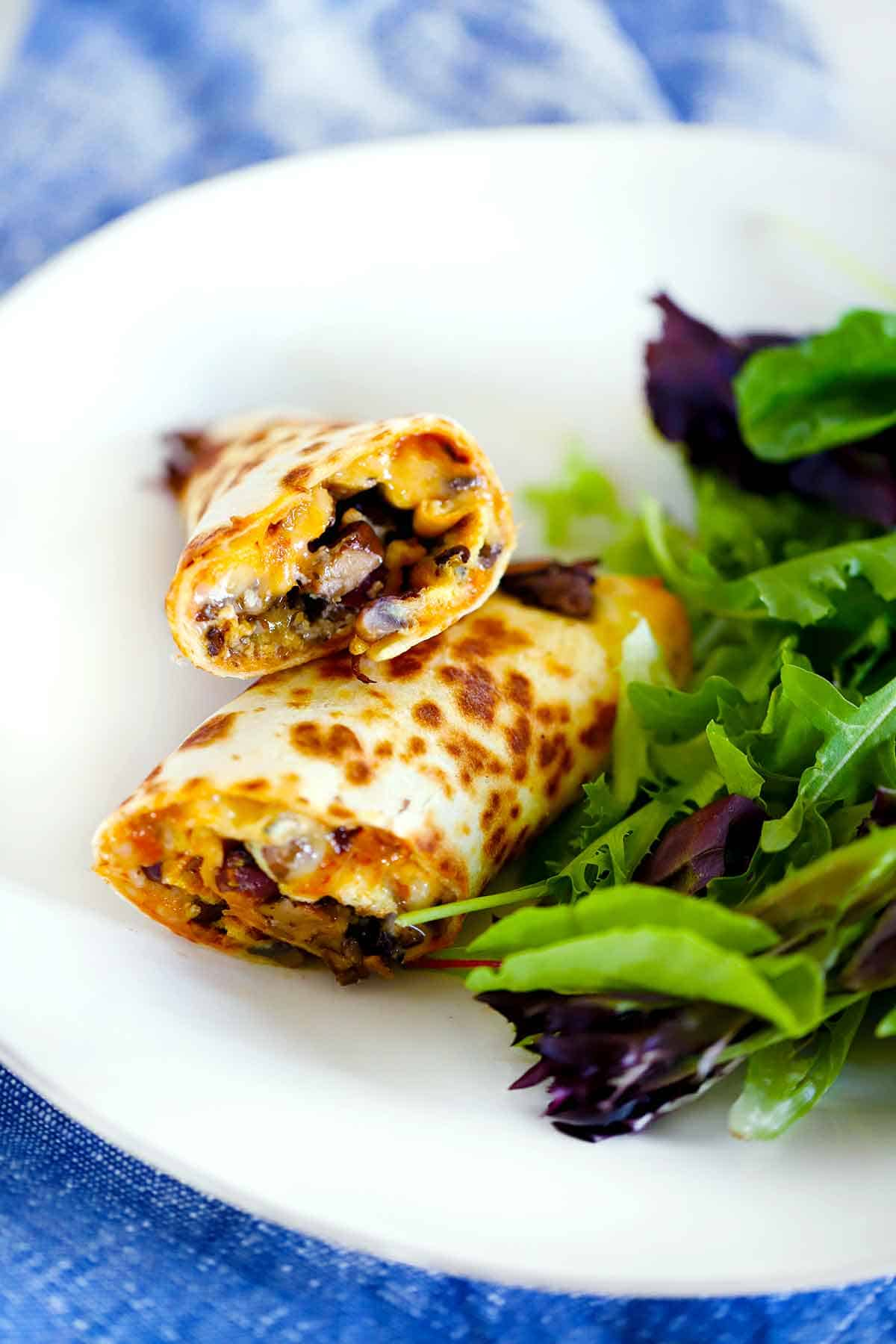 Egg wraps with mushrooms and olives cut in half on a white plate with a side of salad.
