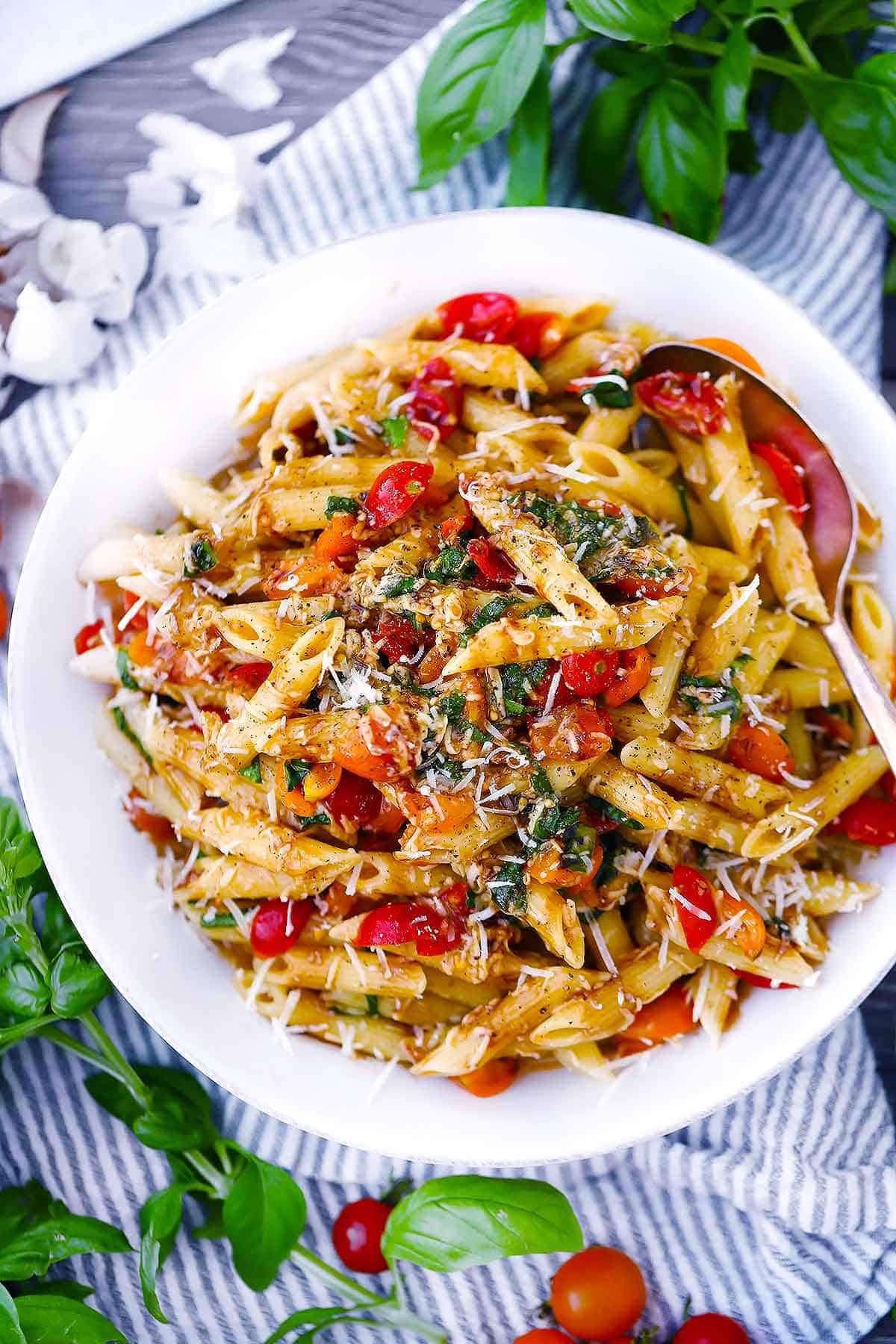 Overhead photo of bruschetta pasta in a white bowl.