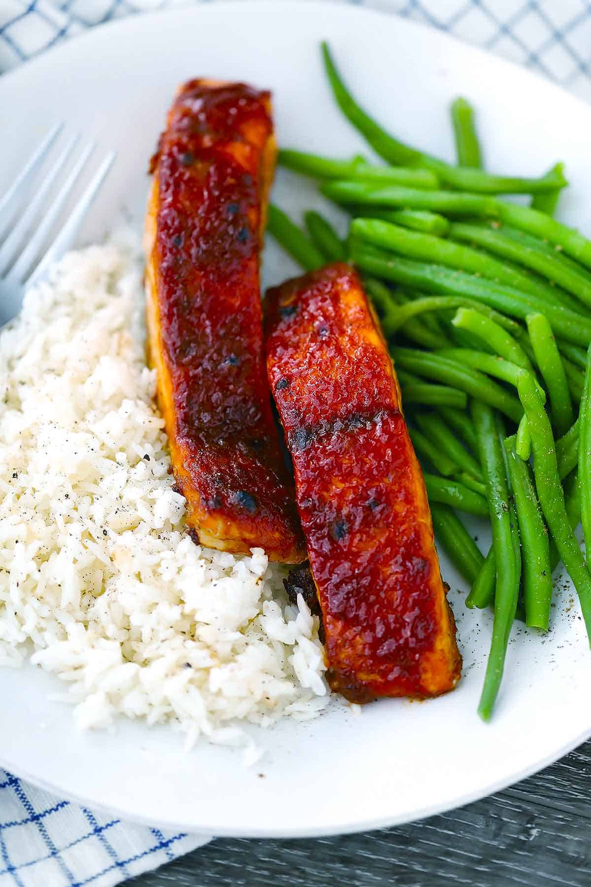 A plate of barbecue salmon with green beans and rice.