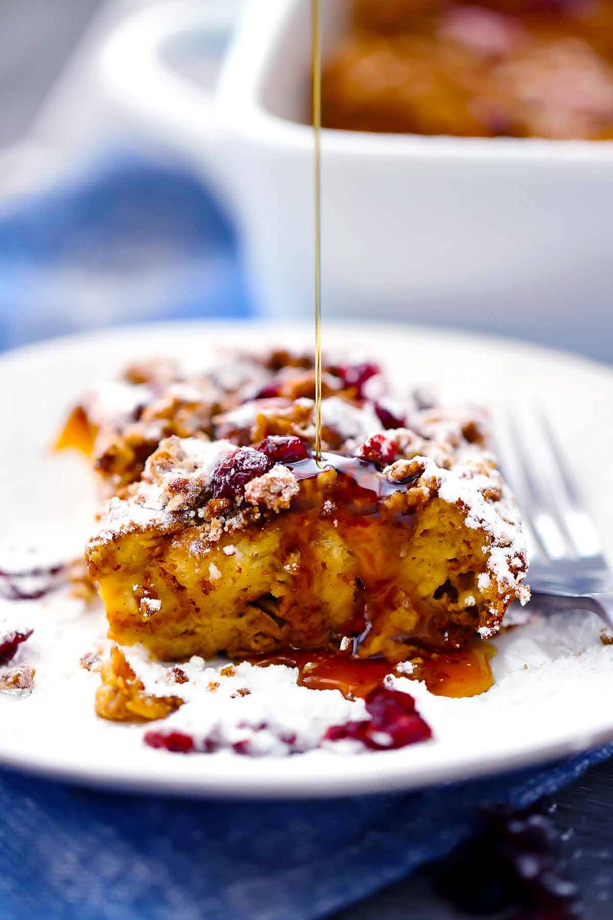 Drizzling maple syrup on a slice of pumpkin french toast casserole.