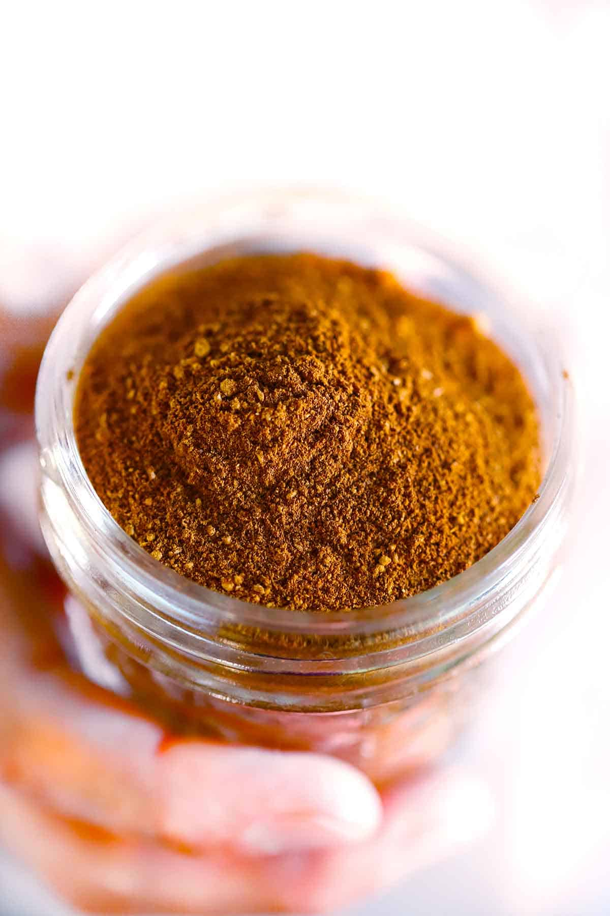 A hand holding a small mason jar of homemade pumpkin pie spice mix.