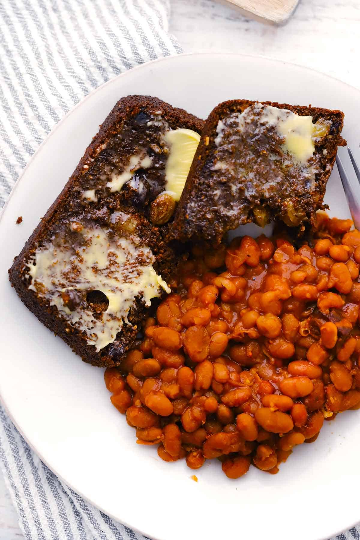 Overhead photo of two slices of brown bread and beans on a white plate.