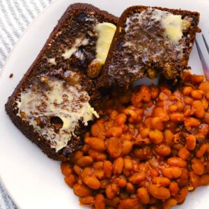 Square photo of two slices of Boston brown bread and beans on a plate.