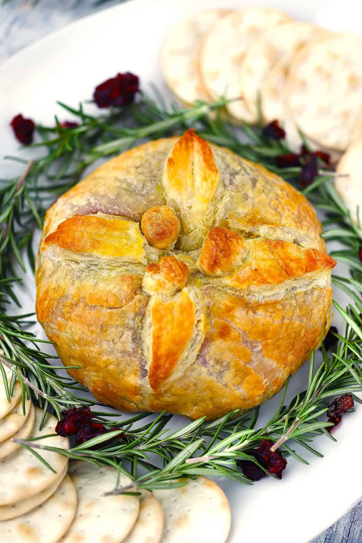 A baked brie en croute decorated with puff pastry leaves and berries on a platter with rosemary, cranberries, and water crackers around it.