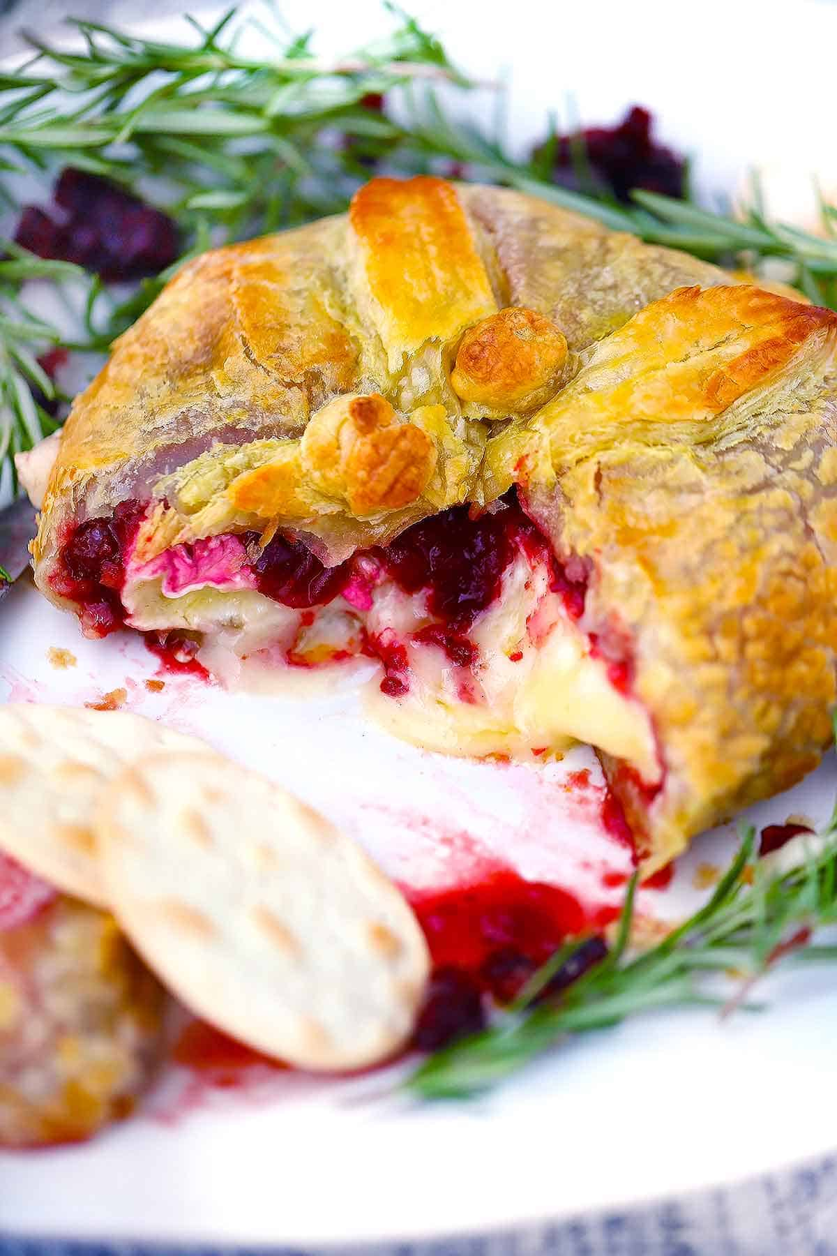 A baked brie en croute on a platter with water crackers, rosemary, and cranberry, sliced open with cheese melting out.