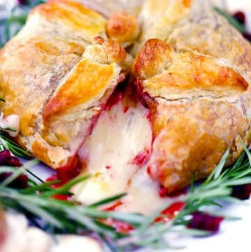 Square photo of baked brie en croute with cranberry sauce with a slice cut out.