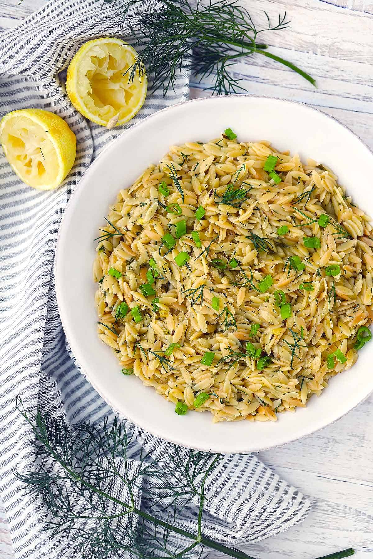 Overhead photo of orzo pilaf in a white bowl topped with green onions and dill with lemon on the side.