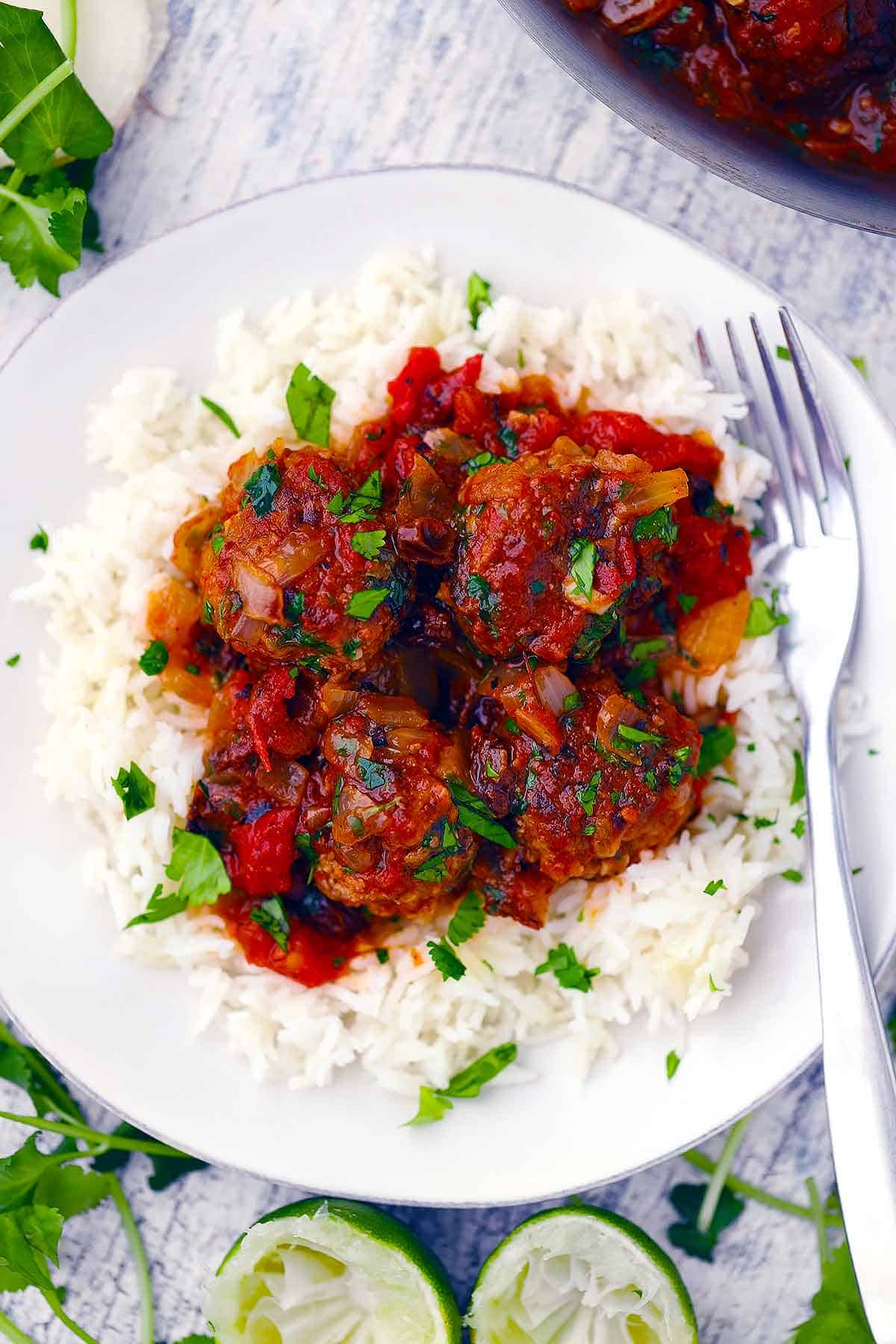 A white plate with lamb meatballs over rice and a fork.