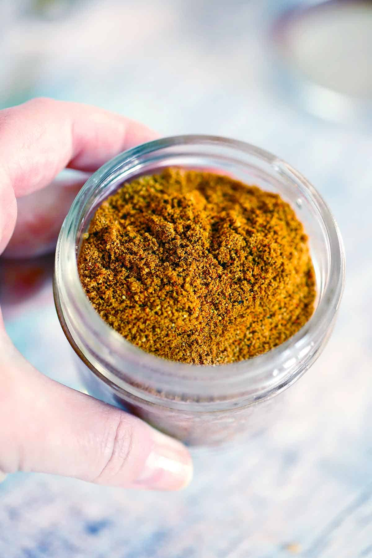 A hand holding a small jar filled with Ras el Hanout.