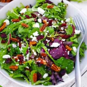 Square photo of a green salad with goat cheese, cranberries, and pecans.