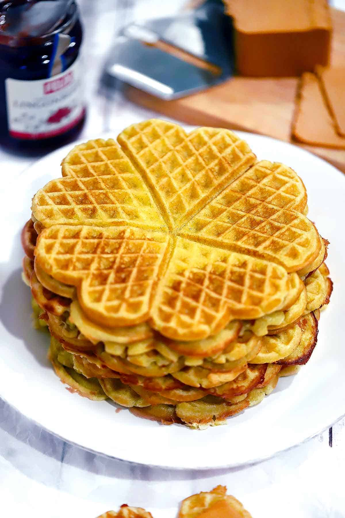 A stack of heart-shaped Norwegian waffles on a white plate with brown cheese in the background.