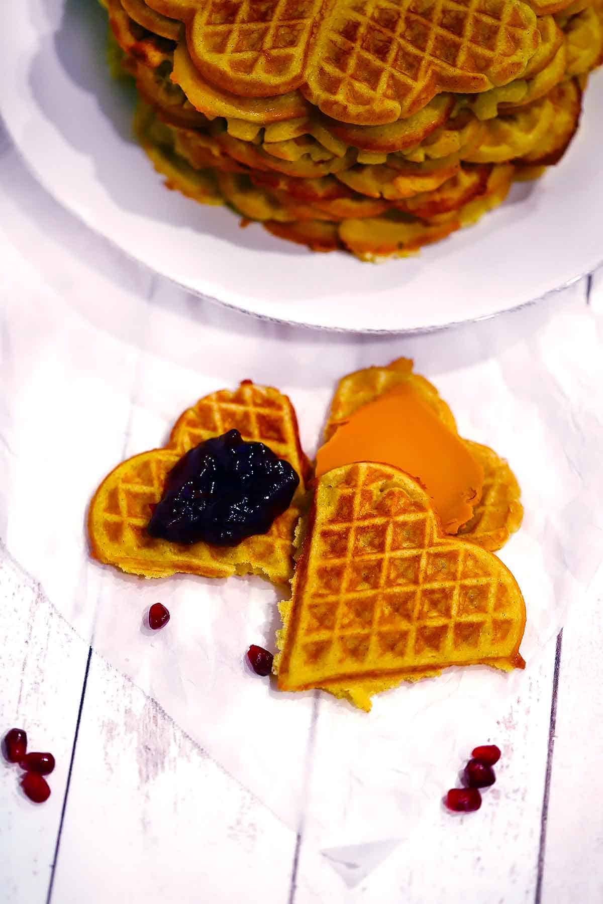 Three heart shaped Norwegian waffles topped with lingonberry jam and brown gjetost cheese.
