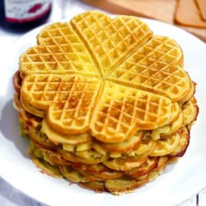 Square photo of heart shaped Norwegian waffles on a white plate.