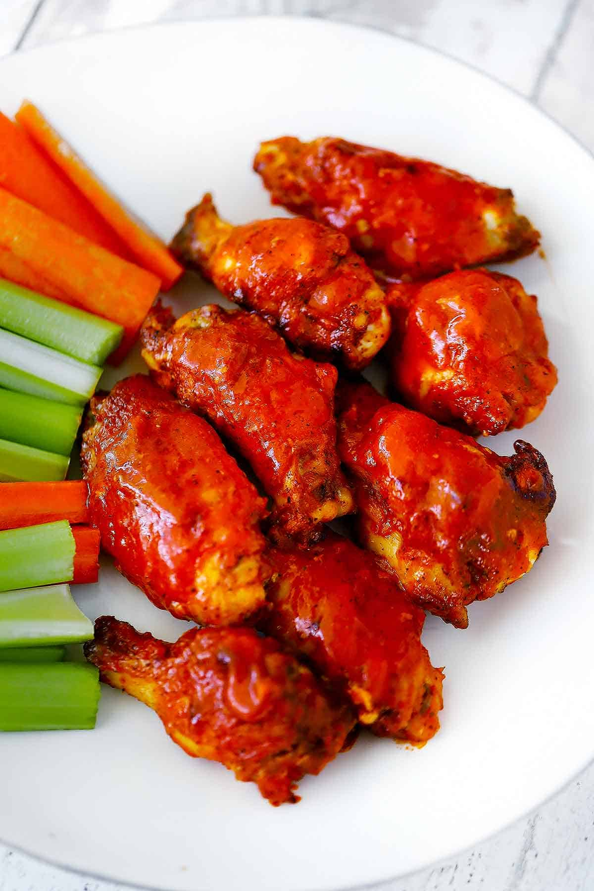 A white plate with buffalo wings, celery, and carrot sticks.