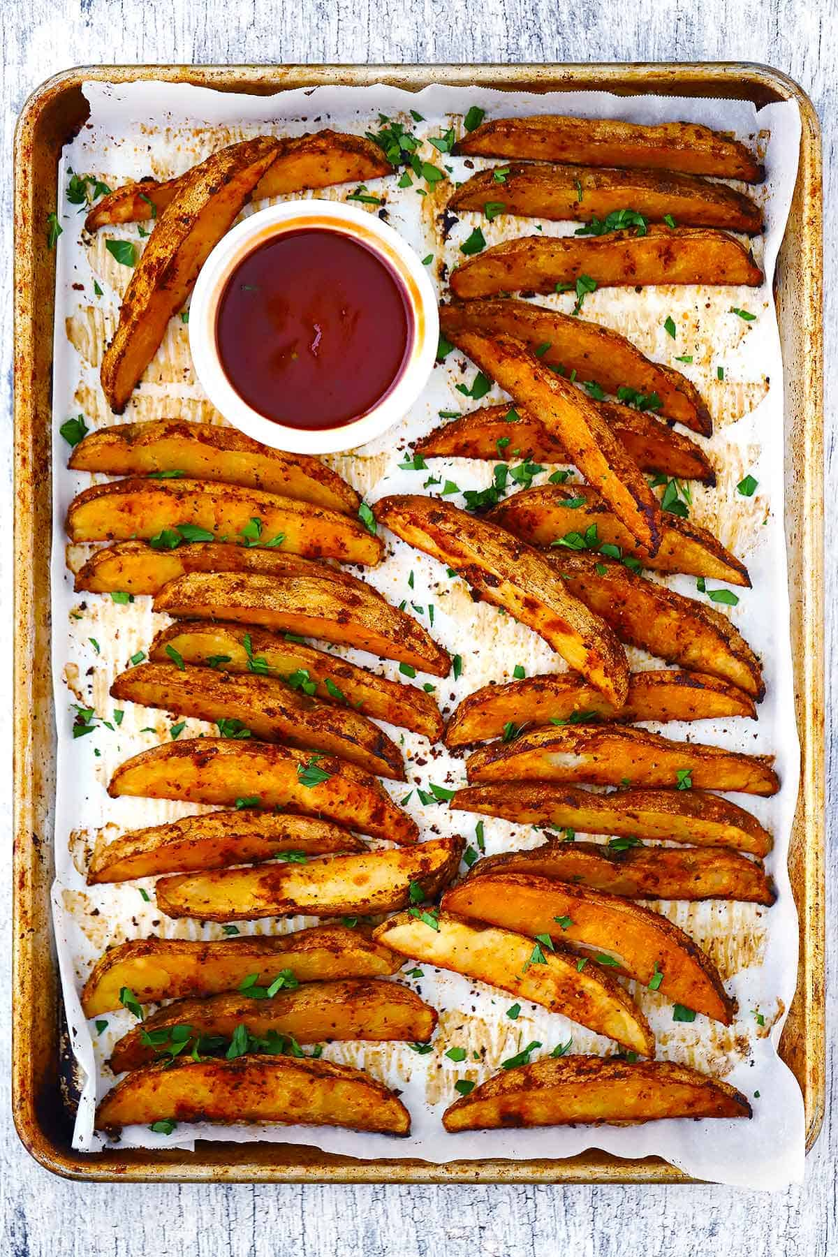 Overhead photo of a sheet pan with crispy potato wedges and bbq sauce on parchment paper.