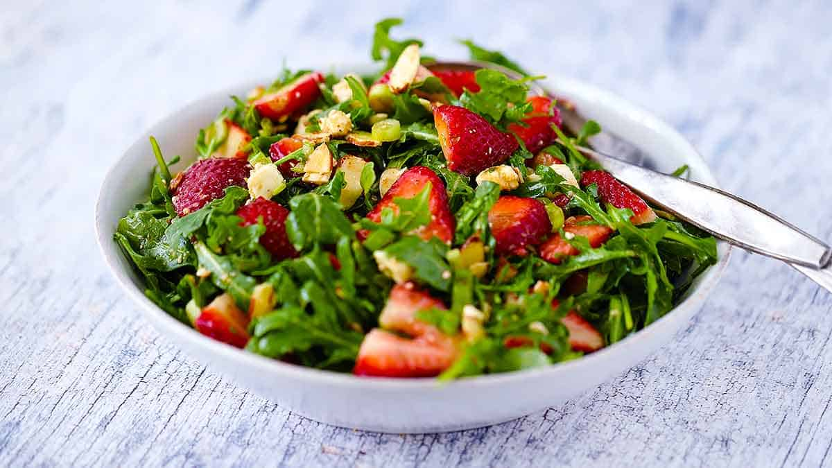 Horizontal photo of a bowl of strawberry arugula salad with feta and balsamic vinaigrette.