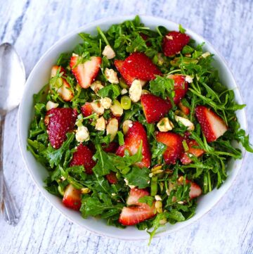 Overhead square photo of a bowl of arugula salad with strawberries.